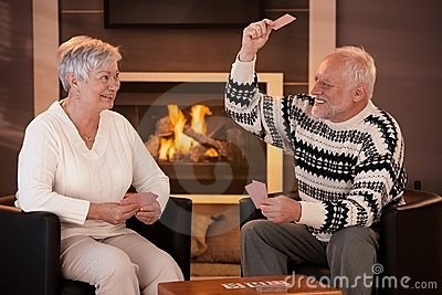 stock photo of Hide the Pain Harold aggressively playing cards with wife