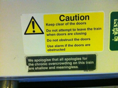 Text - Caution Keep clear of the doors Do not attempt to leave the train when doors are closing Do not obstruct the doors Use alarm if the doors are obstructed We apologise that all apologies for the chronic overcrowding on this train are shallow and meaningless ALE