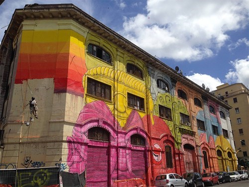 Italian Street Artist Blu Turns a Building Facade Into a Lineup of Cartoony Faces