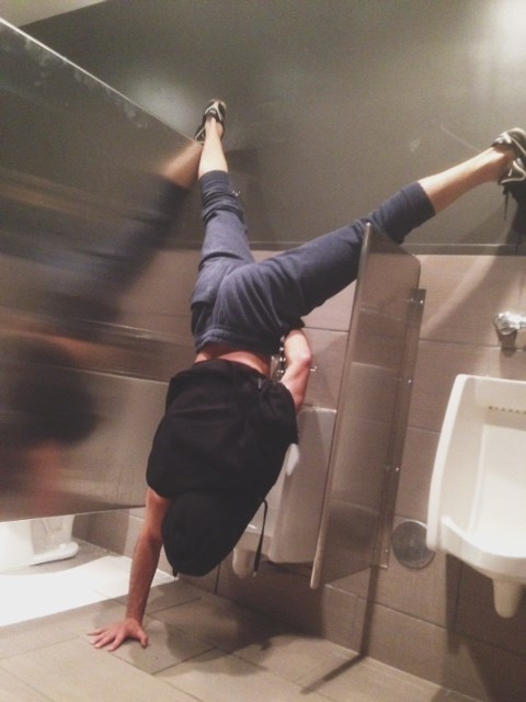 Drunk guy peeing at a urinal doing a handstand