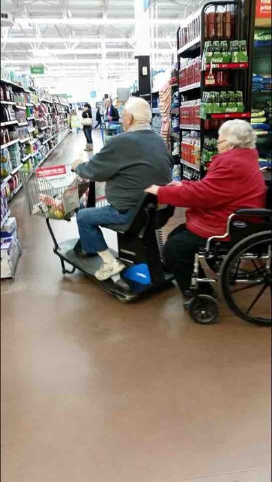 old husband in a rascal pulling his wife in a wheelchair.