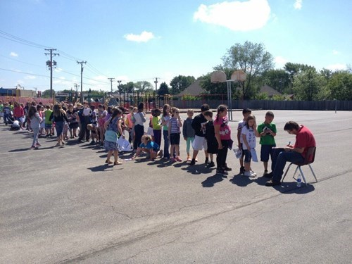 school yearbook image Kids Line Up to Get Their Yearbook Signed by the Janitor