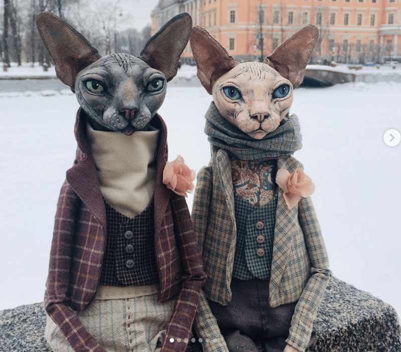 two cat dolls sitting on the snow