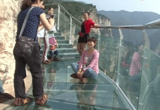 A china mountain glass walkway cracks while tourists walk on it.