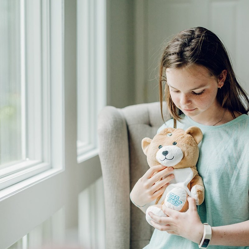 Girl with teddy bear that holds IV bags