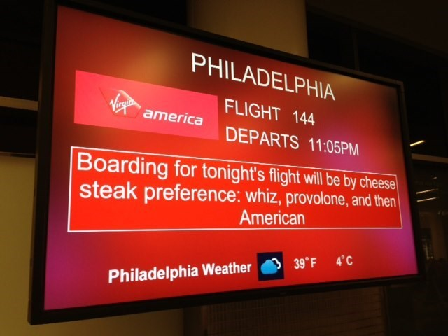 boarding sign - Display device - PHILADELPHIA FLIGHT 144 Virgua america DEPARTS 11:05PM Boarding for tonight's flight will be by cheese steak preference: whiz, provolone, and then American 4 C 39° F Philadelphia Weather
