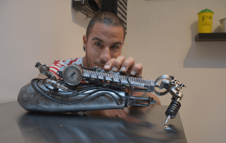 steampunk-esque-prosthetic-arm-draws-tattoos-metal-video