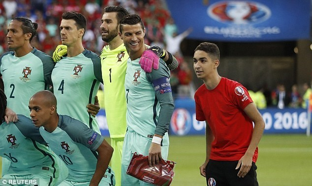 Ball boy photobombs the Portugal's official team photo to the amusement of Cristiano Ronaldo