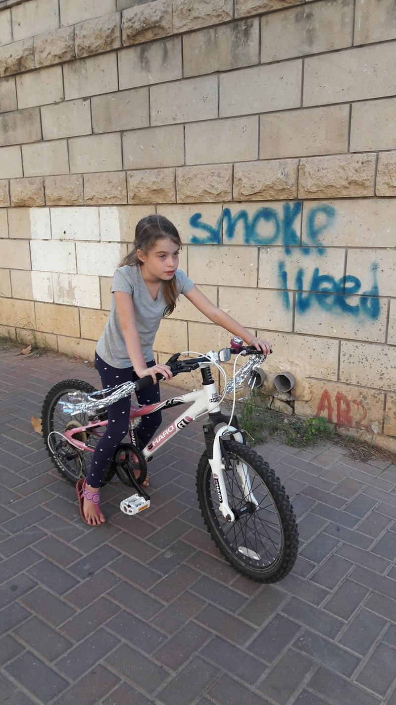 funny parenting image daughter takes picture of new bike next to 420 graffiti