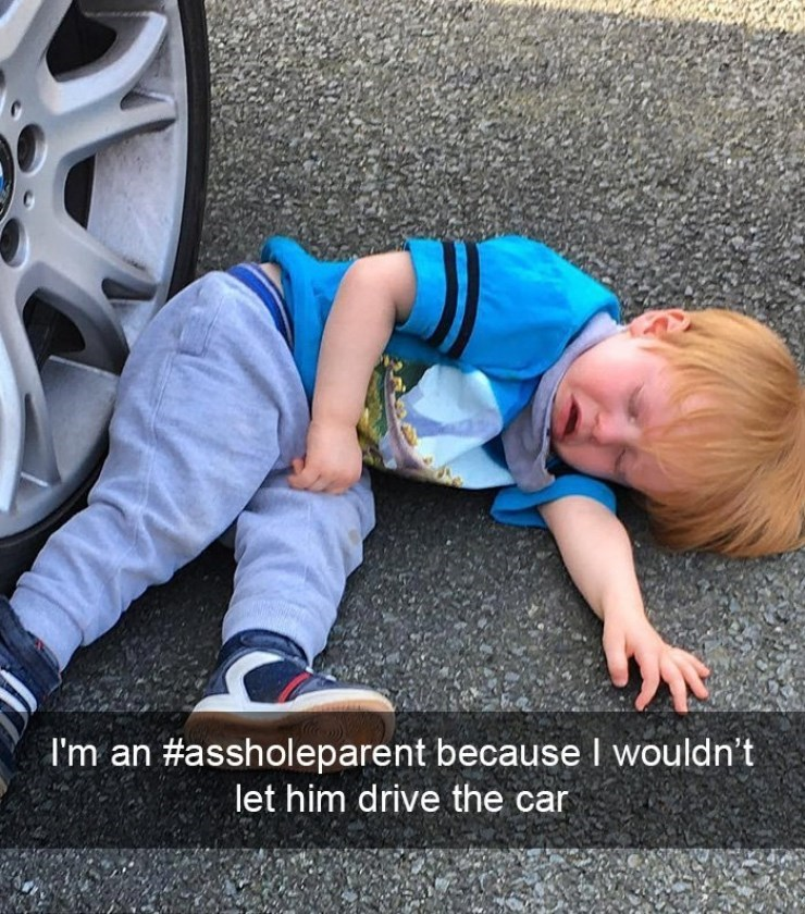 Kid throwing tantrum right next to the car tires because he wasn't allowed to drive the car.
