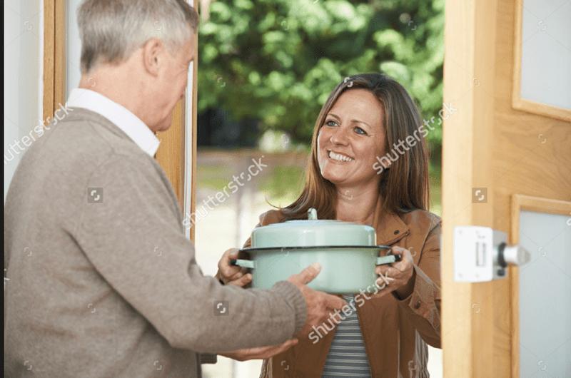 woman giving a man a pot of food