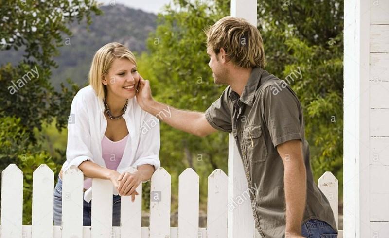 man rubbing his hand against a woman's cheek