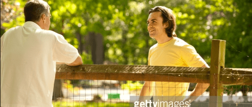 two men talking over a fence