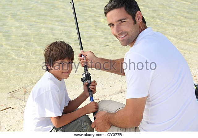 man and son in white shirts sitting by water holding fishing rod