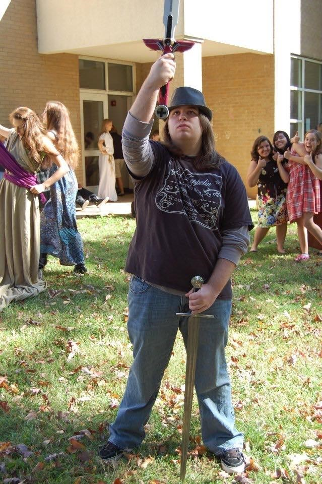 cringeworthy photo of fedora wearer with long hair wielding swords at school