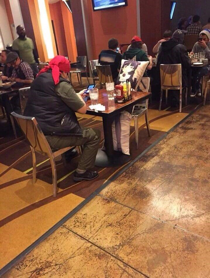 cringeworthy photo in a restaurant of a man having dinner with his waifu