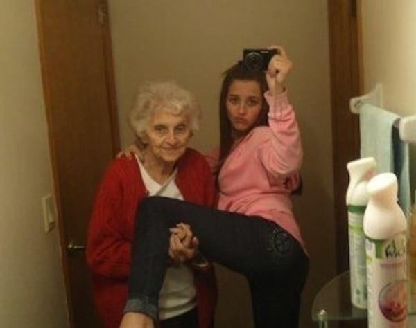 Girl posing with grandma in the bathroom mirror.