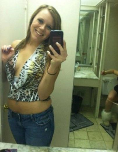Girl posing in the restroom and someone is in the toilette behind her.