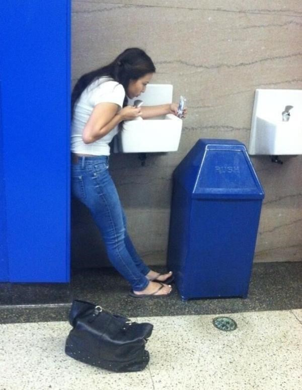 Woman drinking out of a water fountain with strange method