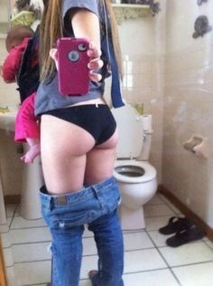Woman holding a baby posing in a backside shot with her pants down.