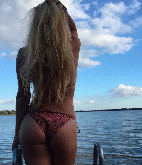 humpday pic of hot girl showing her backside bikini as she stares off at the water