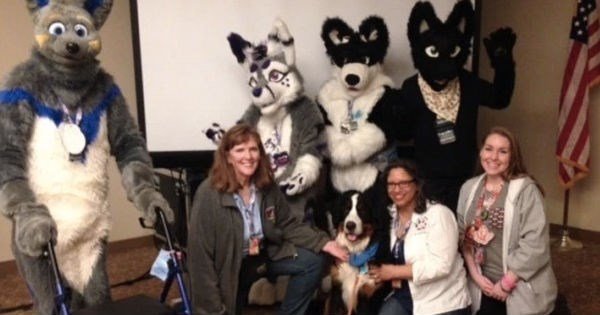 woman posing with furry con members and her dog