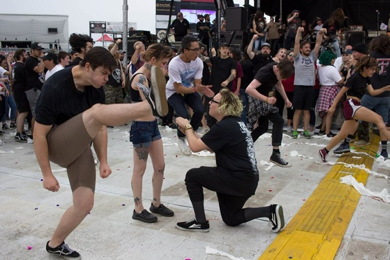 Source for all these funny pictures of a couple getting engaged in the middle of an active mosh pit.