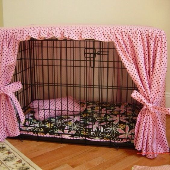 Dog cage with pink curtains.