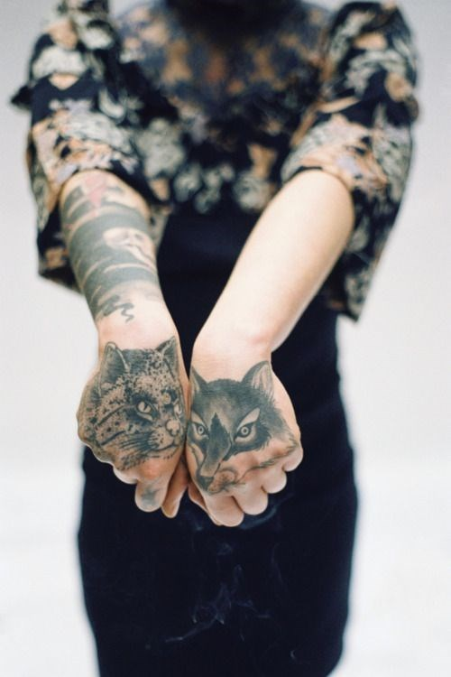 Woman with cat tattoo on one hand, dog tattoo on the other hand.