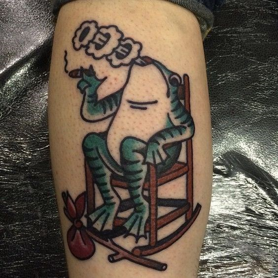 Tattoo of a frog in a rocking chair smoking a cigar.