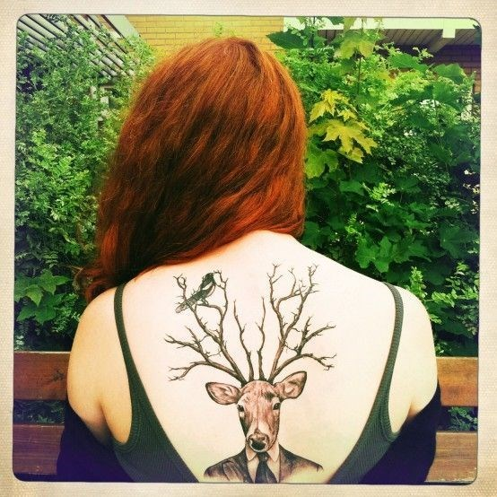 Tattoo on a woman's back of a deer in a suit with large antlers on which a bird is perched.