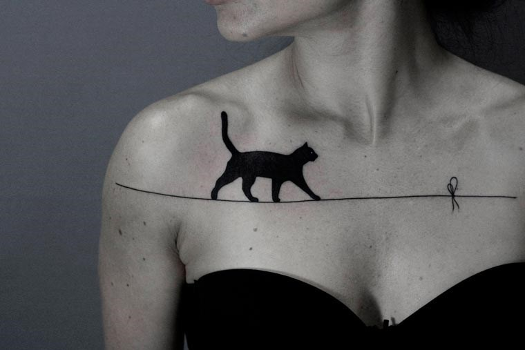 Tattoo of a cat walking across a wire on a woman's upper chest.