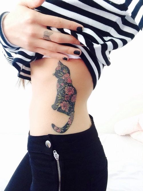Skinny girl with tattoo of a cat made up of flowers on the side of her torso.