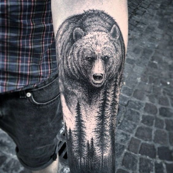 Tattoo of bear in the woods on someone's arm.