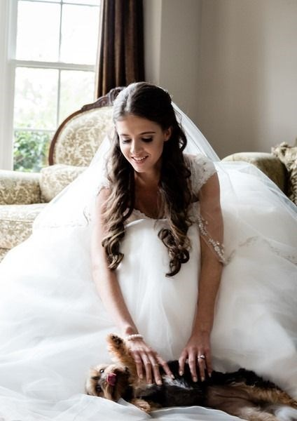 Bride scratching the belly of a dog lying on her fluffy white dress.
