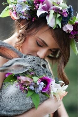 Bride with flowers in her hair kissing a bunny.