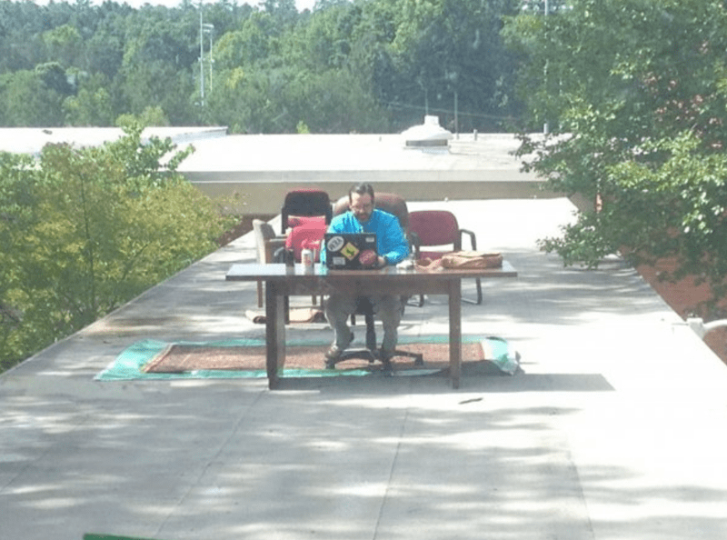Students move teacher's desk outside on roof of school.