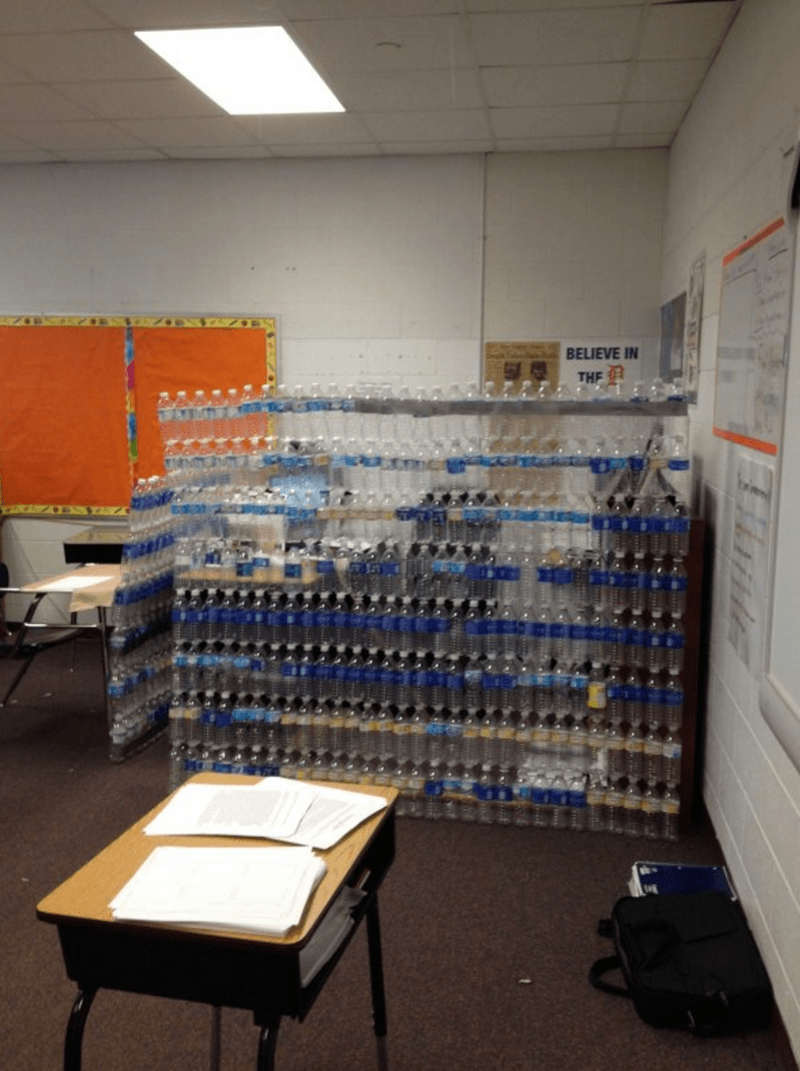 Students build wall of empty water bottles around teacher's desk.