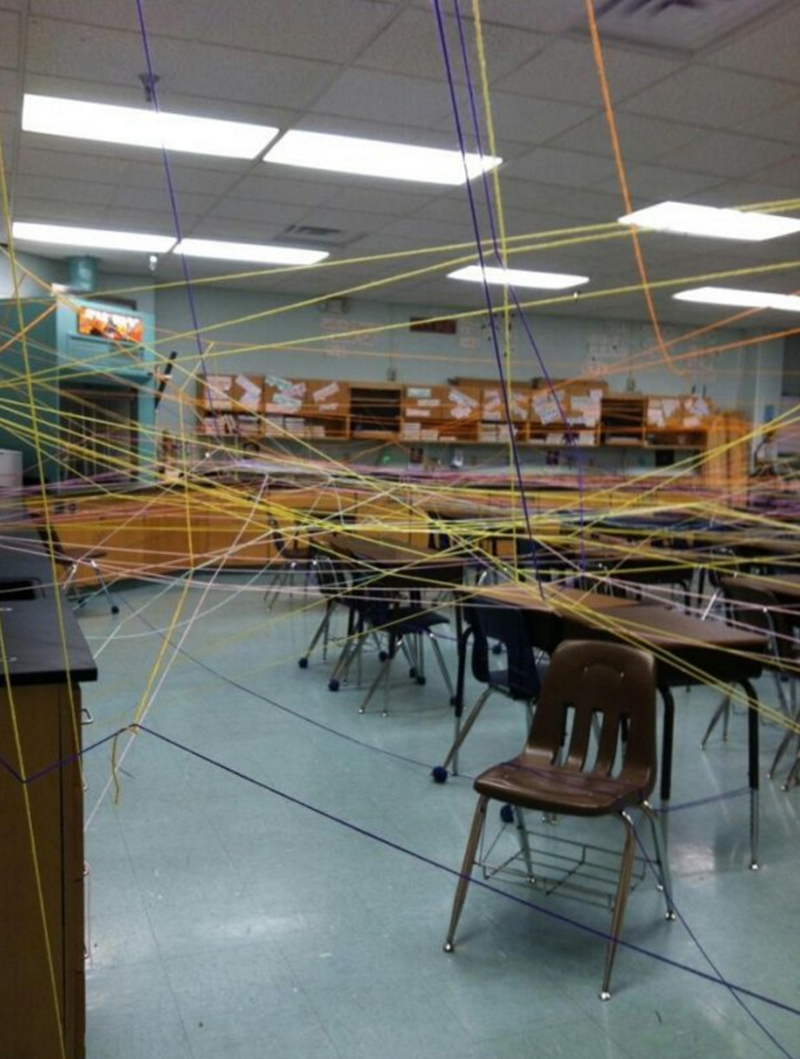 Students create web of yarn in classroom.