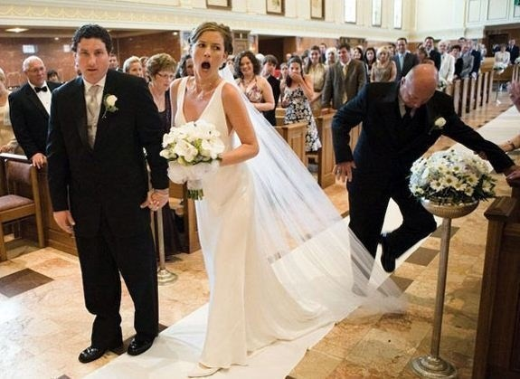 funny pic of man stepping on a bride's veil