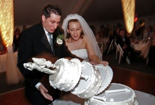 funny pic of a bride and a groom next to a fallen wedding cake