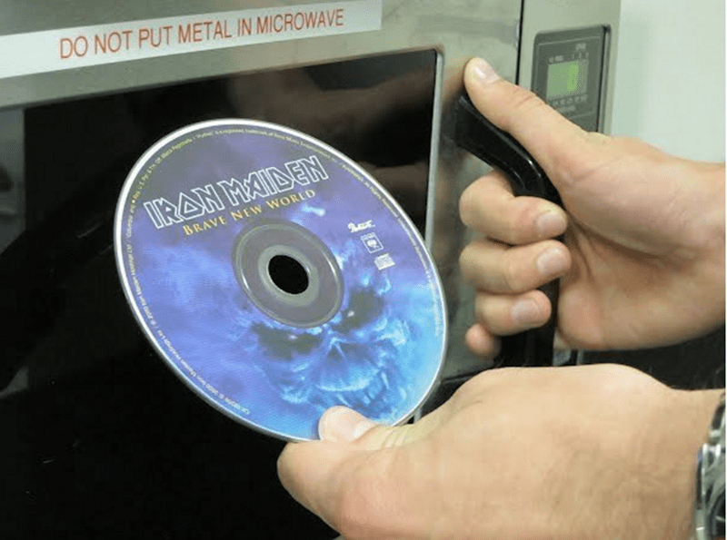 Person is about to put in Iron Maiden disc into microwave when it says to not put metal in there.