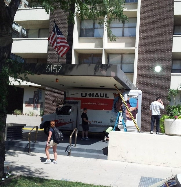 Funny fail picture of a U-Haul truck stuck under the buildings awning.