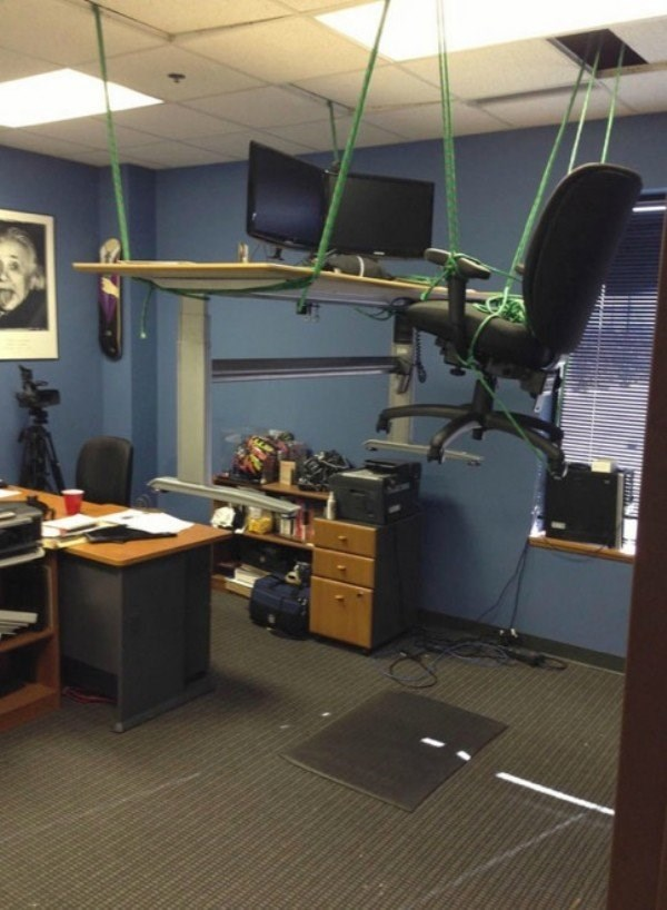 Workplace prank someone did of elevating the entire office desk and chair off the floor.