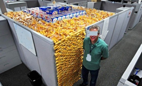 Office prank of filling a workers cubicle to the top with snacks.