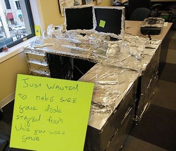 Office prank of entire desk covered with tin foil.