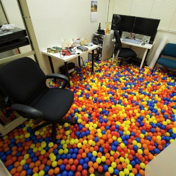office space filled with plastic balls like a ball pit.