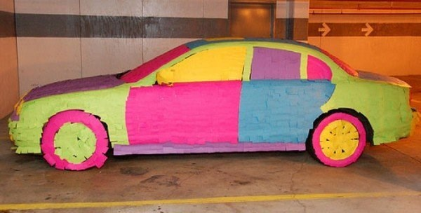 Office prank of car covered with colorful post-it notes.
