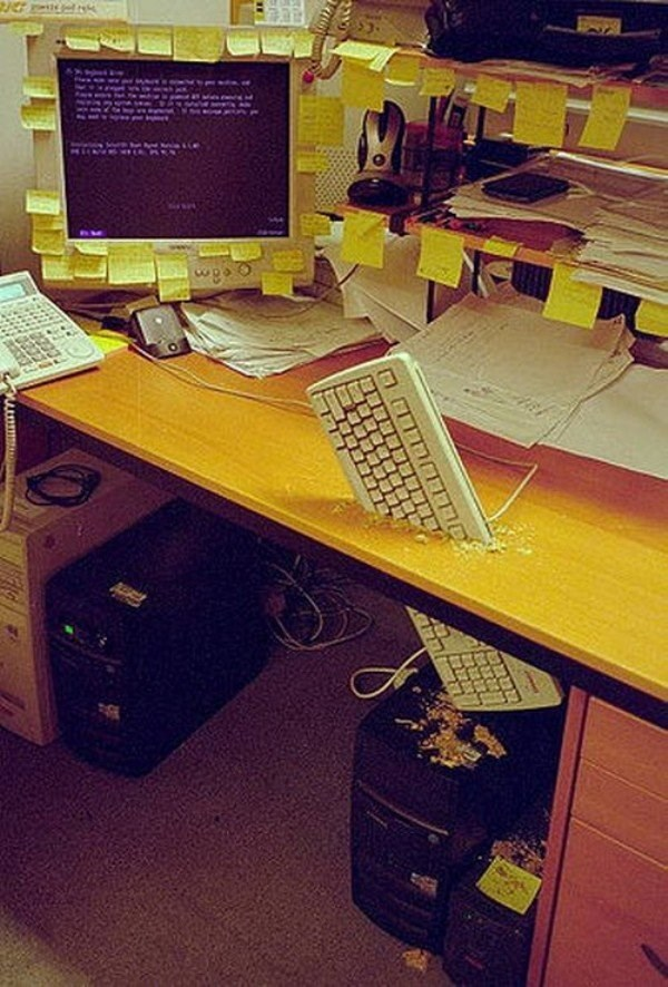 Office prank of keyboard punched through the desk of the computer.