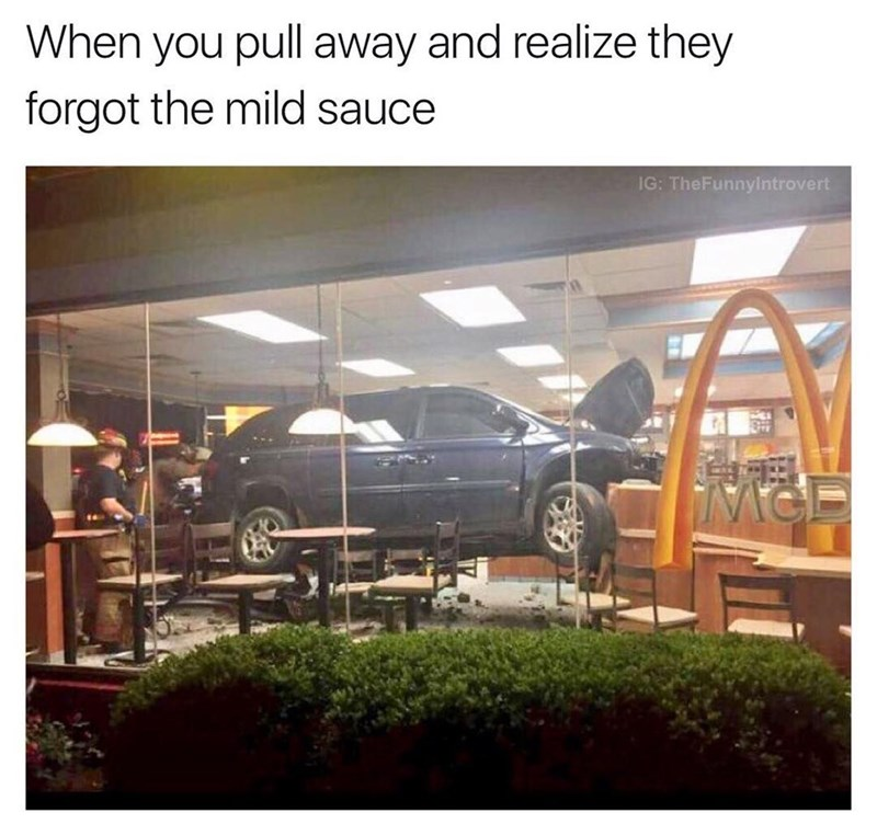 Funny picture of a car that crashed into the middle of a McDonalds restaurant captioned about forgetting the mild sauce.